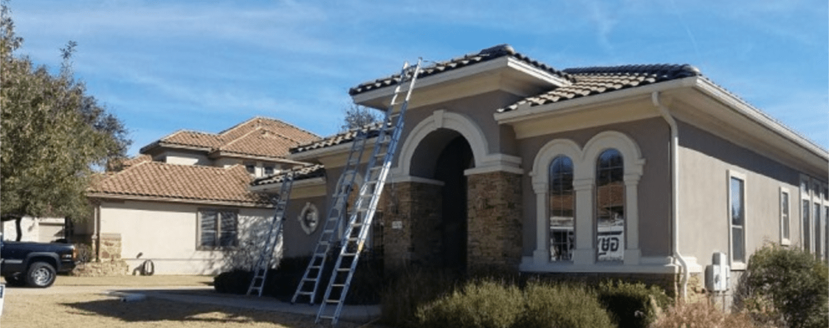 Seamless Rain Gutters - Lakeway, TX - Installing white rain gutters on two-story brick house with ladders