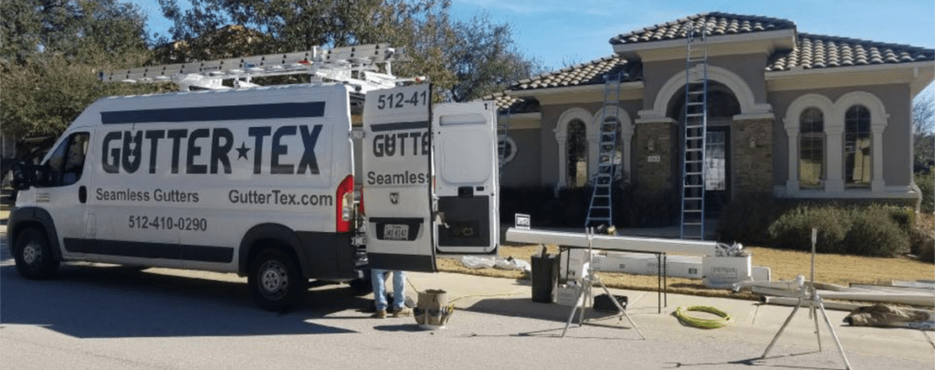 Seamless-Gutter-Service-Kyle-TX-Gutter-Tex-Company-van-and-seamless-gutters-in-front-of-house