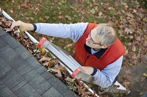 Gutter Guards - Gutter Tex - Austin, TX - Man on ladder cleaning leaves from gutters